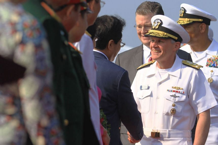 Vice Admiral Phillip G. Sawyer (right), commander of the US Navy's Seventh Fleet, greets Vietnamese officials after the US aircraft carrier USS Carl Vinson pulled into port in Danang on March 5, 2018.