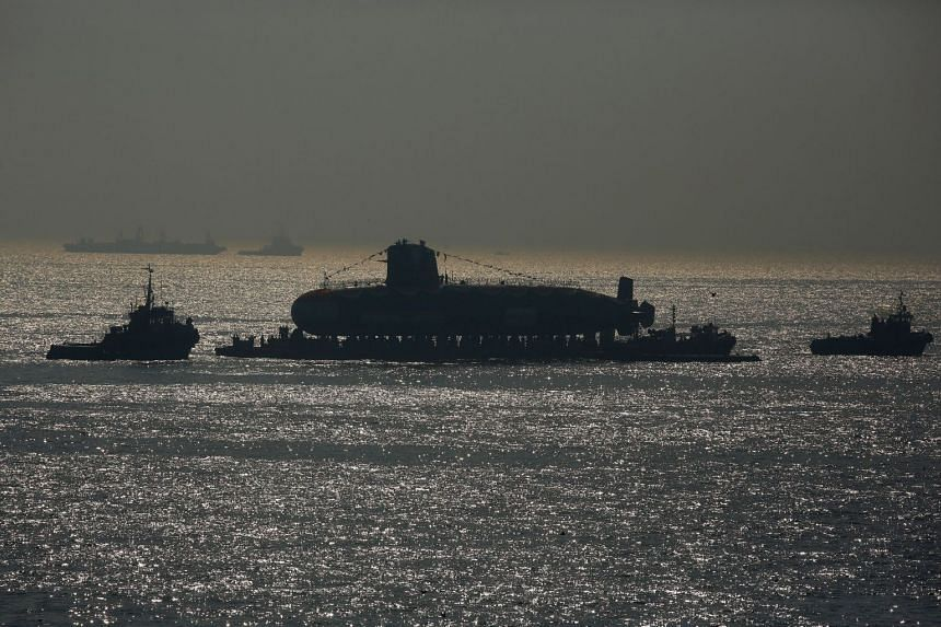 India's third Scorpene-class submarine INS Karanj is seen silhouetted as a tugboat pulls it in Mumbai, India, on Jan 31, 2018.