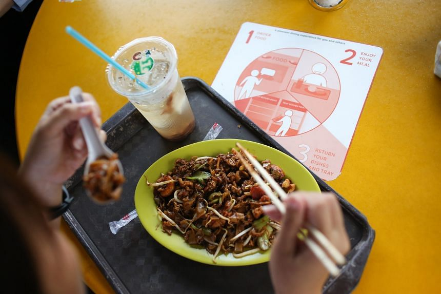 Stickers on tables at Zion Riverside Food Centre remind patrons to return their trays and dirty cutlery to designated tray-return stations.