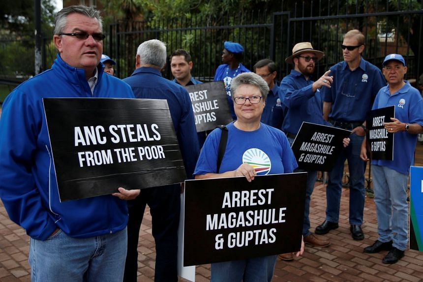 Protesters outside a South African court where people arrested during a raid on the Gupta family home were due to appear.