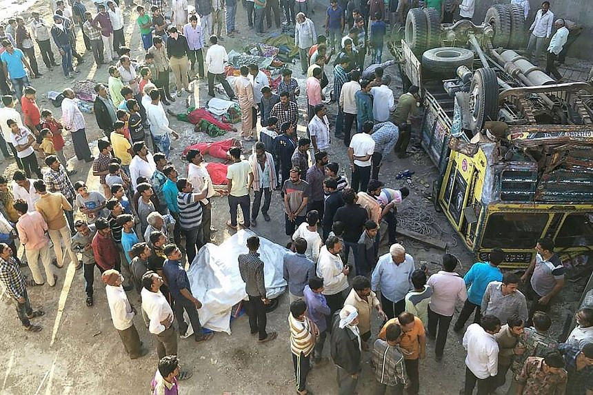 Onlookers gathering around the bodies of passengers who had been travelling in a lorry that plunged off a bridge in western India yesterday. At least 30 people - mostly women and children - died when the lorry, carrying a wedding party, fell off the