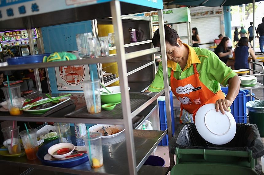 At Zion Riverside Food Centre, cleaners' aprons carry messages reminding patrons to return their food trays. The daily return rate improved four months after these reminders were introduced around the food centre.