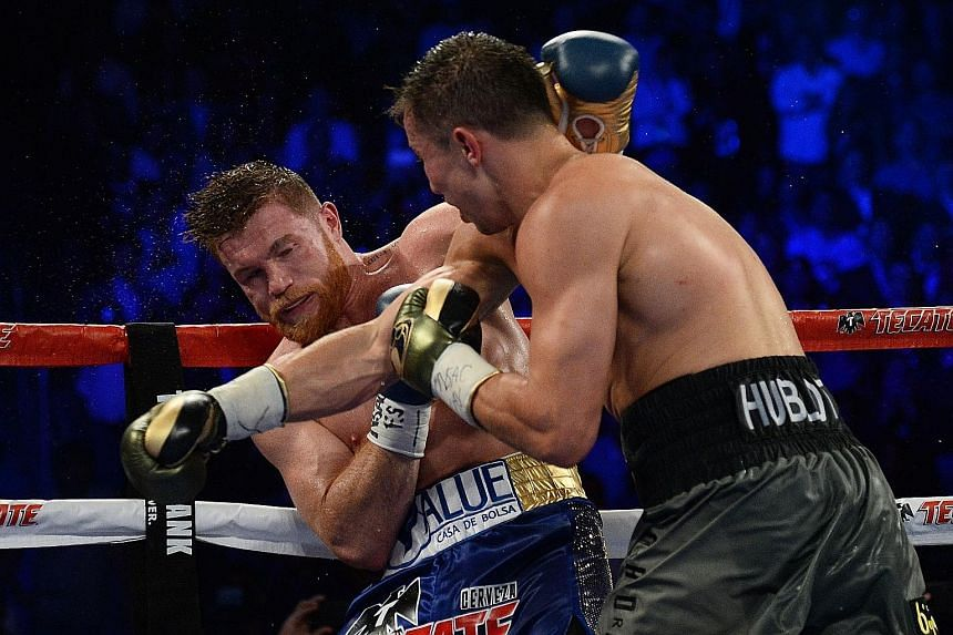 """Saul """"Canelo"""" Alvarez (blue trunks) taking a punch from Gennady Golovkin during their drawn world middleweight championship fight in September. The rematch could still go ahead in May, despite Alvarez failing a drug test."""