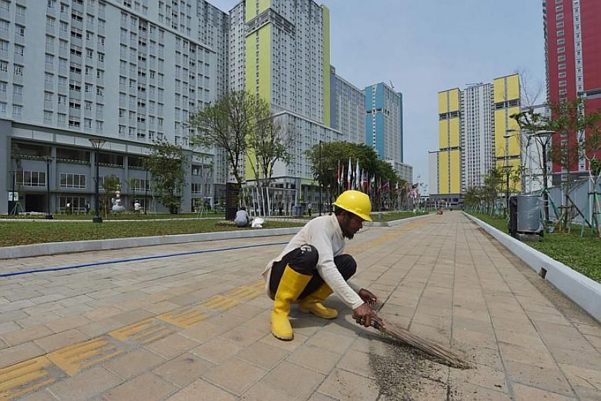 An Indonesian worker cleans an outdoor area of the athlete village in preparation for the Asian Games in central Jakarta on Feb 26, 2018.