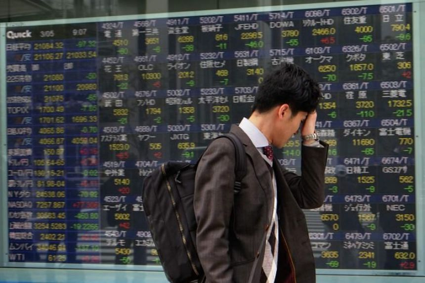 A pedestrian walks past an electronics stock indicator in Tokyo on March 5, 2018.