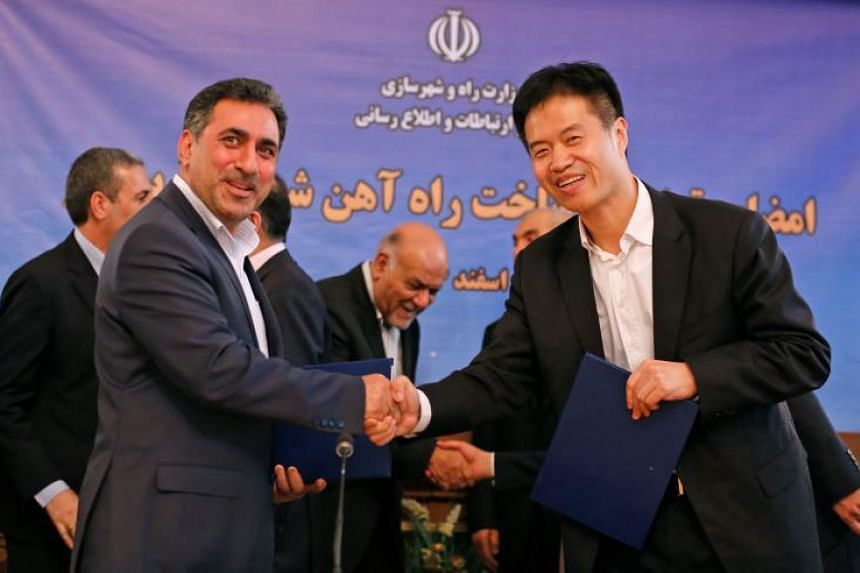 Kheirollah Khademi (left), Iran's deputy minister for roads and urban development shakes hands with Yang Chuanliang, executive president of China Machinery Industry Construction Group Inc. in the capital Tehran on March 7, 2018.