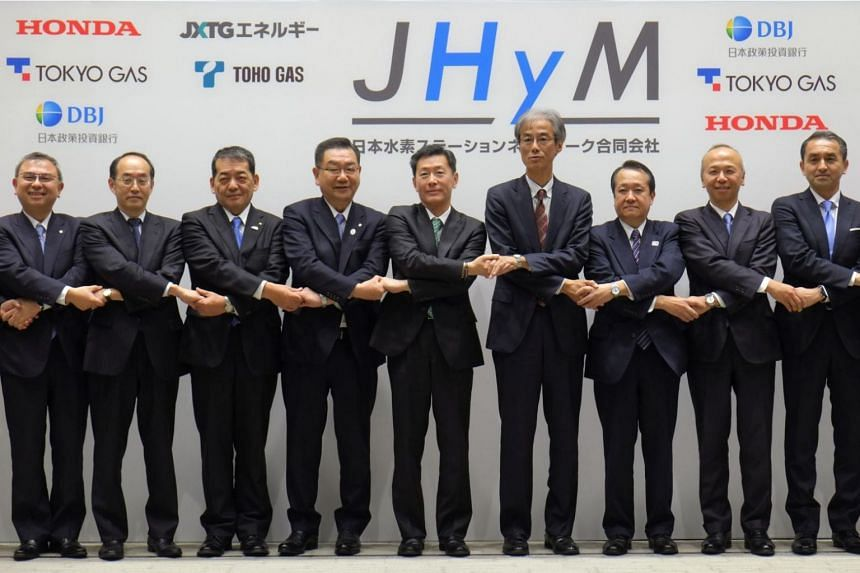 Japan H2 Mobility President Hideki Sugawara (fifth from left) and representatives of its joint establishment companies hold hands during a photo session after their joint press conference in Tokyo on March 5, 2018.