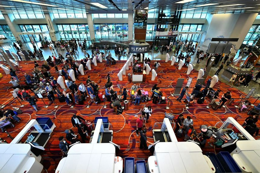 All travellers at Changi Airport, such as those shown using self-service kiosks at Terminal 1, will soon have to pay $13.30 more in departure fees when flying out of Changi.