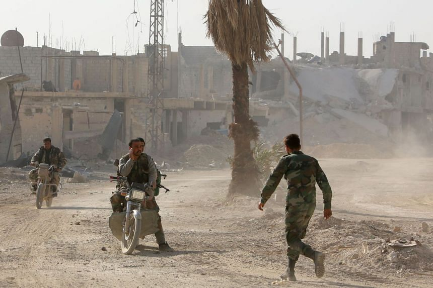 Syrian government forces are seen in the former rebel-held area of Beit Nayem in Eastern Ghouta.