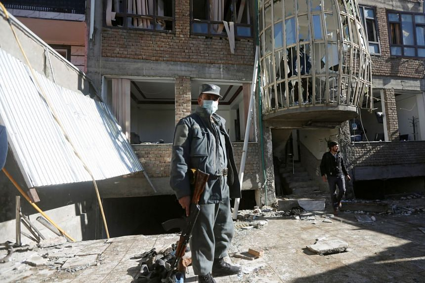 An Afghan policeman keeps watch at the site of a suicide attack in Kabul, Afghanistan, on Dec 28, 2017.