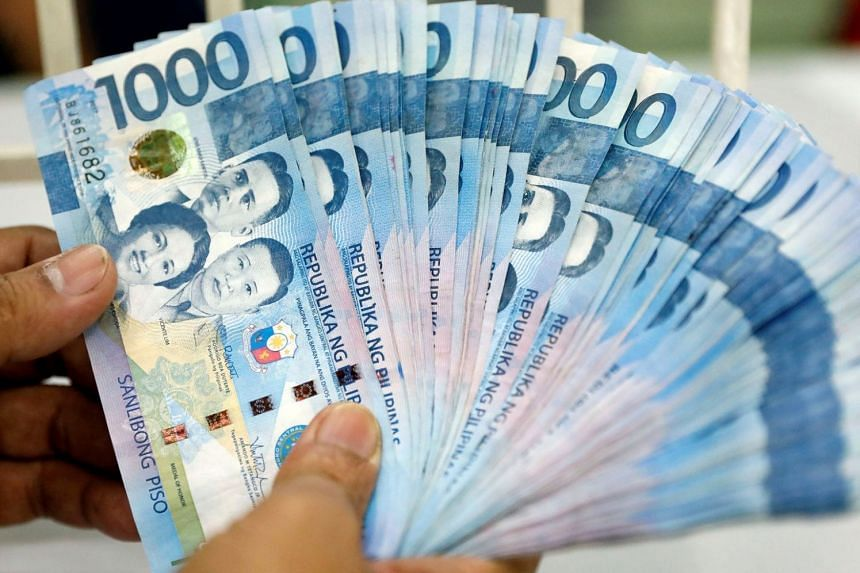 A Worker Shows Philippine Peso Bills Inside Money Changer In Metro Manila Philippines On