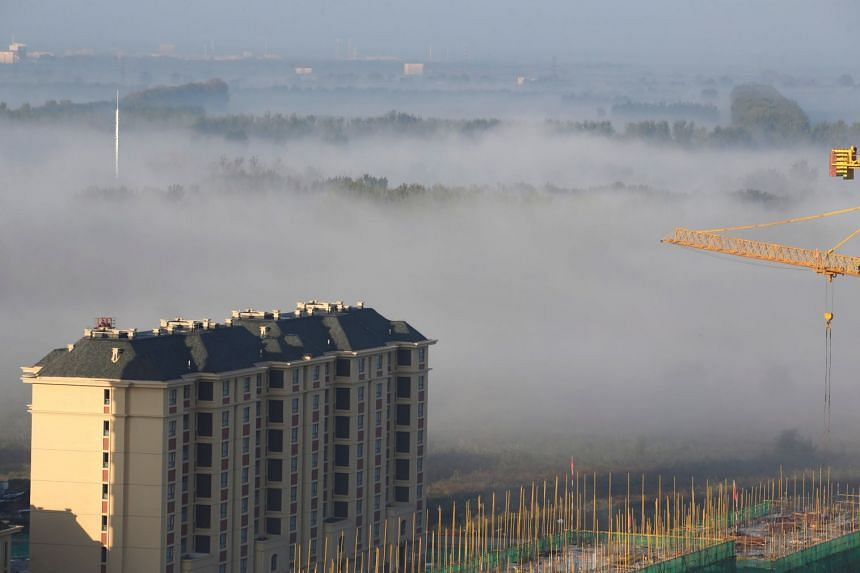 Apartment blocks are seen in smog on the outskirts of Tianjin, China, on Oct 11, 2017. Tianjin Party Chief Li Hongzhong said the city would stick to its zero tolerance for polluting industries.