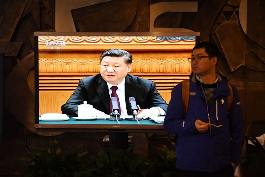 Footage of Chinese President Xi Jinping is seen on a TV screen in the media centre for the ongoing annual National People's congress, China's legislature in Beijing on March 6, 2018.