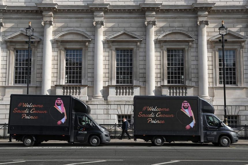 Vans featuring a welcome to the Crown Prince of Saudi Arabia Mohammad bin Salman are parked in Whitehall in central London on March 7, 2018.