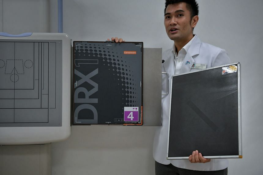 Radiographer Harris Abdul Razak, 31, showing the difference between the old Computed Radiography Cassette (right) and the new Digital Radiography Imaging Plate (centre) at Ang Mo Kio Polyclinic on March 7, 2018.