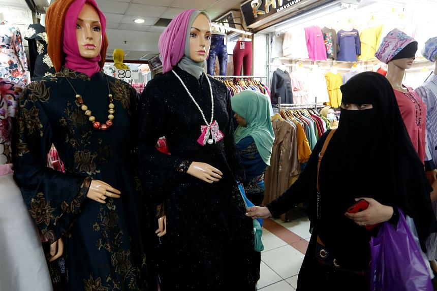 A woman wearing a full-face veil shops for clothes in a traditional textile market in Jakarta, Indonesia, on March 7, 2018.