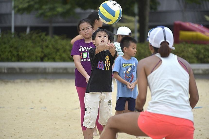 Left: The Sports Hub's water festival this weekend will enable families to immerse themselves in different activities, including surfing on the Stingray. Below: Children learning how to play volleyball last year at the sandpit, where there will be a