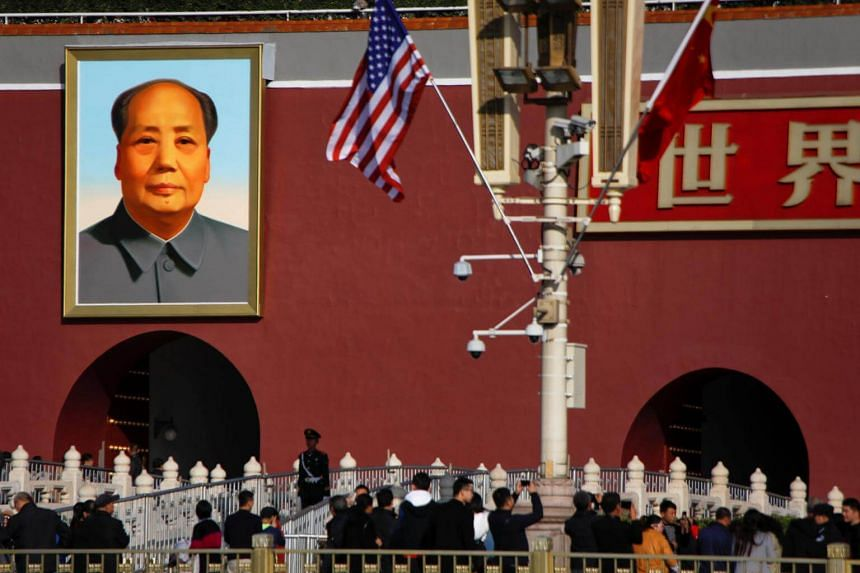 The flags of the US and China flutter in front of a portrait of late Chinese Chairman Mao Zedong at the Tiananmen gate in Beijing.