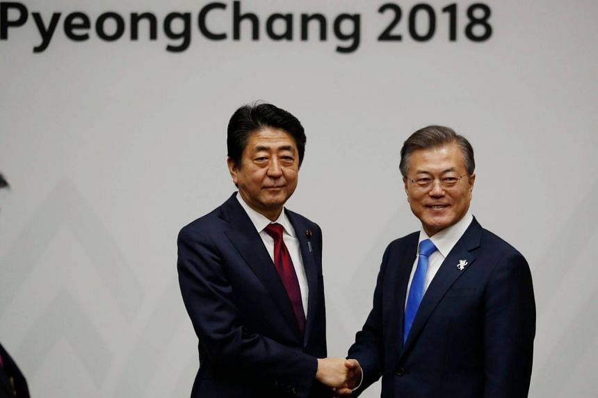 Japan's Prime Minister Shinzo Abe (left) with South Korea's President Moon Jae In during their meeting in Pyeongchang, South Korea on Feb 9, 2018.