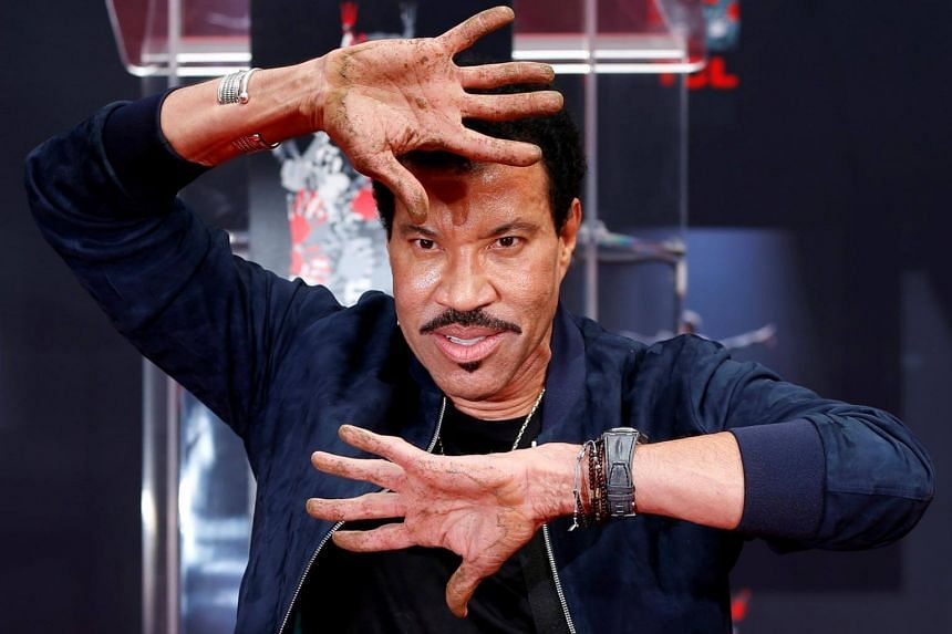 Recording artist Lionel Richie shows his hands after placing them in cement during a ceremony in the forecourt of the TCL Chinese theatre in Los Angeles, California, US  on March 7, 2018.