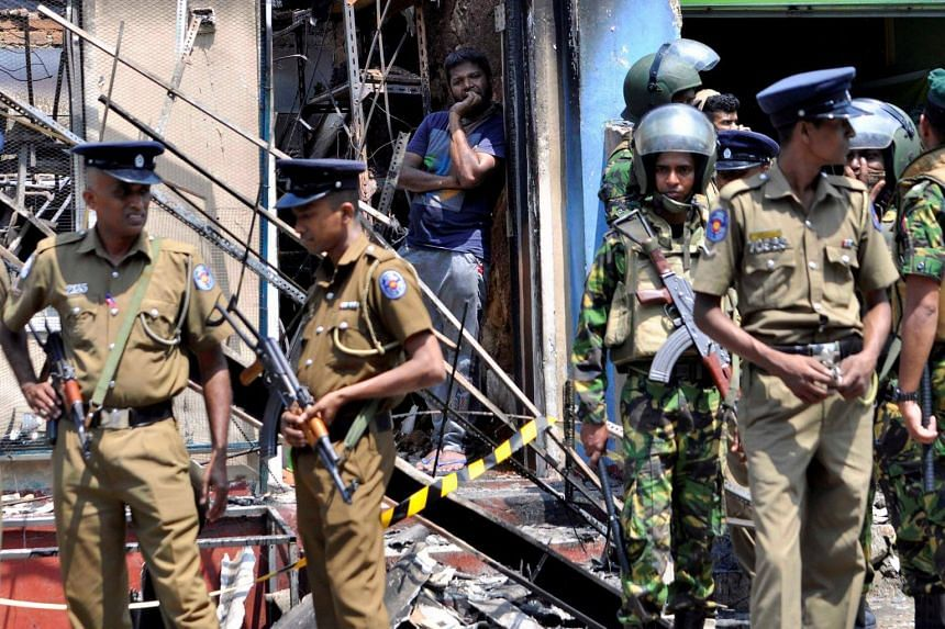 Sri Lanka's Special Task Force and police officers stand guard near a burnt house after clashes in Digana, Sri Lanka, on March 6, 2018.