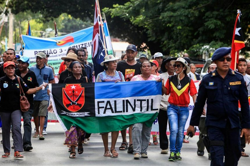 People holding banners in reaction to an agreement to end the maritime dispute between the East Timor and Australia.