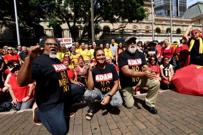Wangan and Jagalingou traditional owners and their supporters shout slogans during a protest outside Parliament House in Brisbane, Australia, on March 8, 2018.