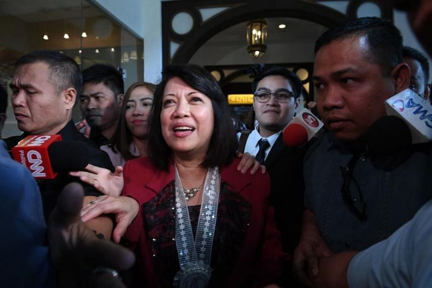 Philippine's Chief Justice Maria Lourdes Sereno (centre) talks to reporters after attending the annual convention of the country's judges in Manila on March 8, 2018.
