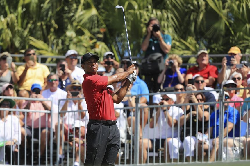 Woods plays his tee shot on the first hole during the final round of the Honda Classic.