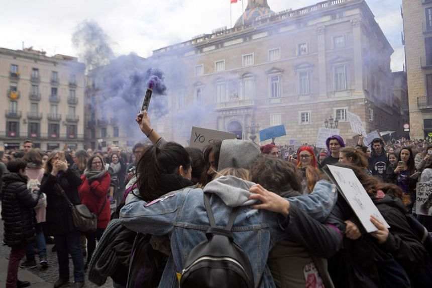 Demonstrators hold up a smoke flare as they gather at the Sant Jaume square during a one-day strike to defend women's rights on International Women's Day in Barcelona on March 8, 2018.