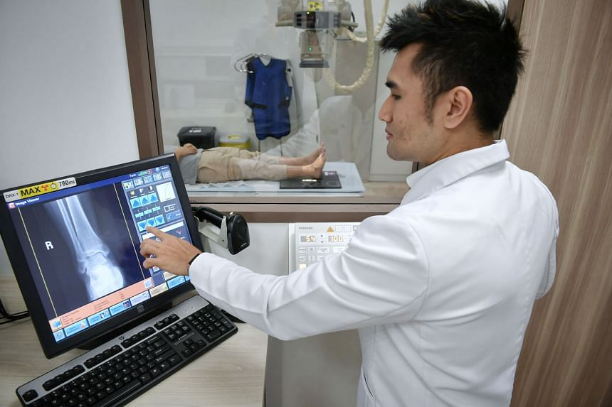 "NHG radiographer Harris Abdul Razak using the digital radiography system to process an X-ray image of a patient's ankle at Ang Mo Kio Polyclinic. X-rays can now be done for 120 patients a day ""without breaking a sweat"", he says, compared to up to 80"