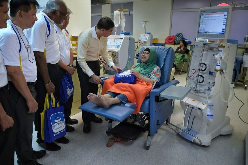 Mr Ang Wei Neng, chief executive of transport group ComfortDelGro's taxi business, with Madam Nor Aisah at the Kidney Dialysis Foundation Bishan Centre on March 8, 2018. On Madam Aisah's left is one of the three new haemodiafiltration machines donate