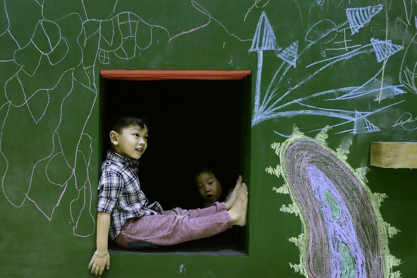 A child peeks out of Down the rabbit, a mixed-media installation by Singapore-based artist Poh Yah See.