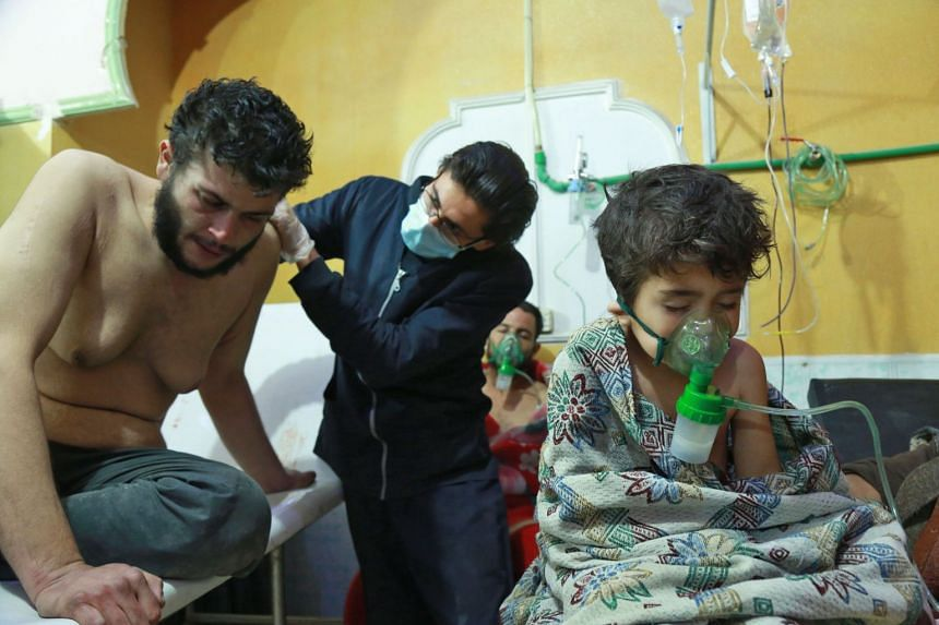 Syrian children and adults receive treatment for a suspected chemical attack at a makeshift clinic on the rebel-held village of al-Shifuniyah in the Eastern Ghoutaregion on the outskirts of the capital Damascus late on Feb 25, 2018.