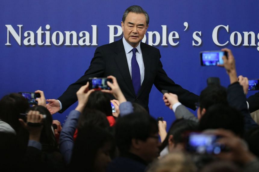 Wang Yi gestures to reporters as he concludes a press conference on the NPC sidelines.