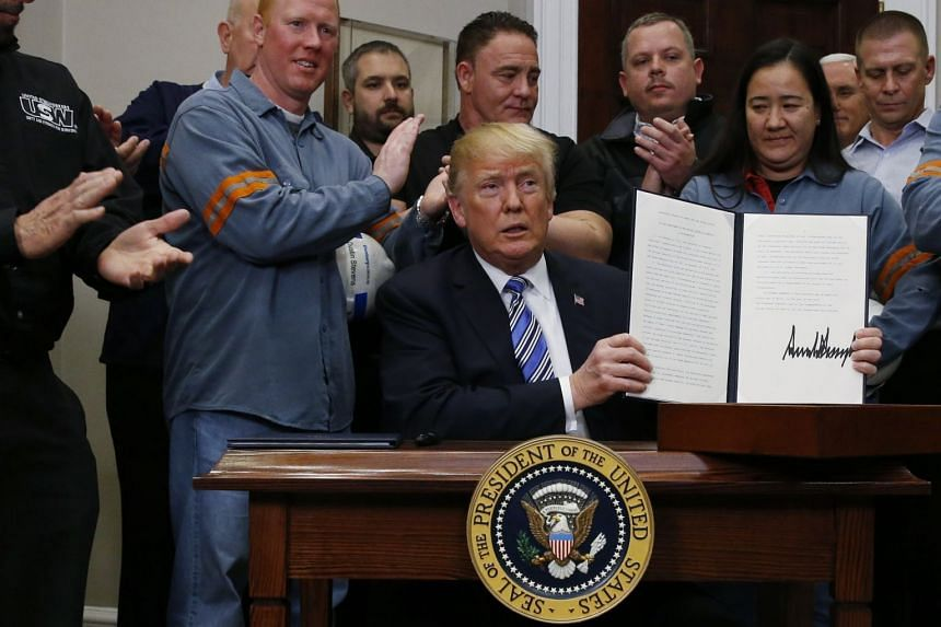 Trump holds up a proclamation during a White House ceremony to establish tariffs on imports of steel and aluminum.