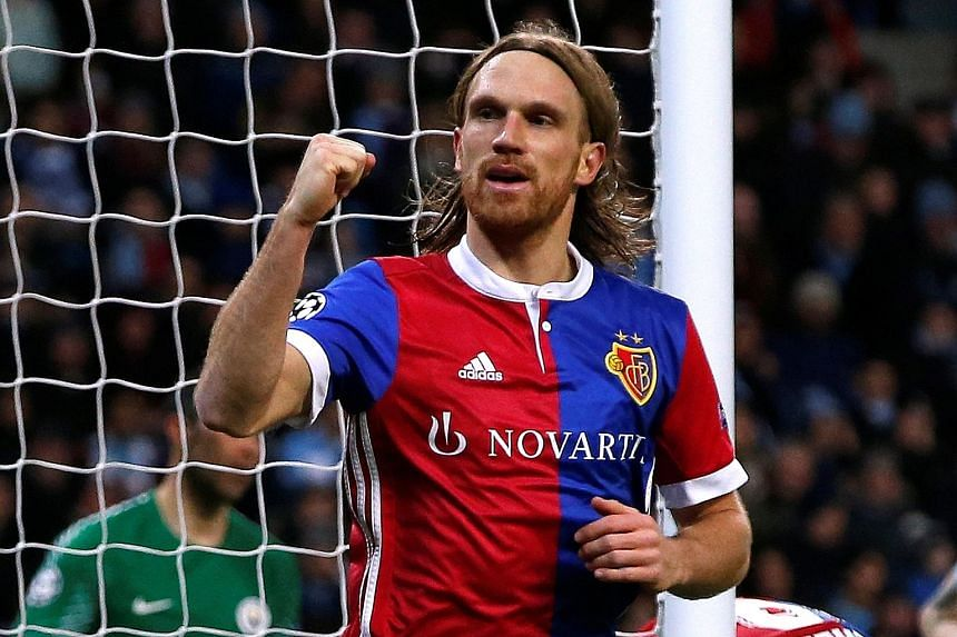 Above: Basel's Michael Lang pumping his fist after scoring his side's winner against a weakened Manchester City. The impact of City's first defeat on their home turf this season was lightened by their 4-0 win in the first leg that meant the English t