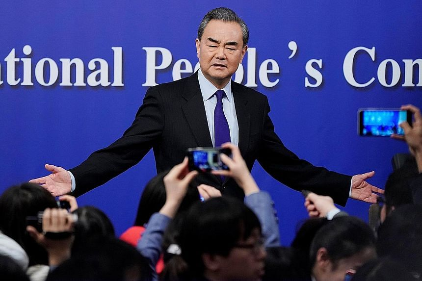 """Mr Wang at a news conference on the sidelines of the National People's Congress yesterday. The minister said """"China is bearing a weighty responsibility for maintaining world peace""""."""