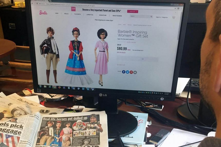 A journalist looks at the new Barbie series Inspiring Women, featuring (from left) Amelia Earhart, Frida Kahlo and Katherine Johnson in New York, on March 7, 2018.