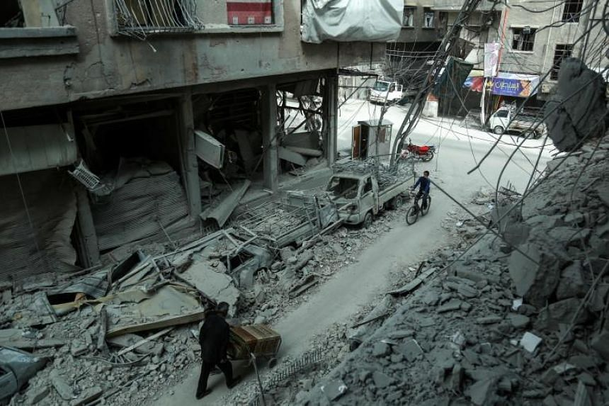 A man pushes a cart as another rides a bicycle past rubble from destroyed buildings down a street in the rebel-held town of Douma in the Eastern Ghouta enclave on the outskirts of Damascus on March 8, 2018.