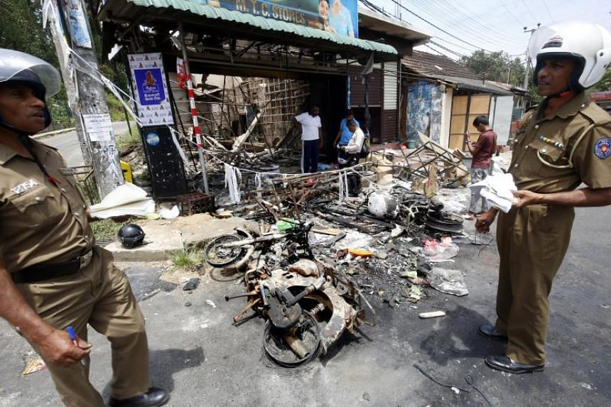 Sri Lankan policemen examine the remains of a business establishment and motorcycles in the riot torn Digana area in Kandy, Sri Lanka, on March 7, 2018.