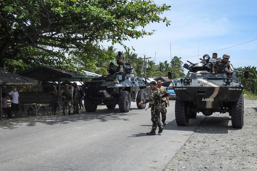 Philippine soldiers standing next to their armoured personnel carriers as they man a checkpoint along a highway near the clash site between government troops and islamic militants in Datu Saudi Ampatuan town, Maguindanao province, on March 8, 2018.