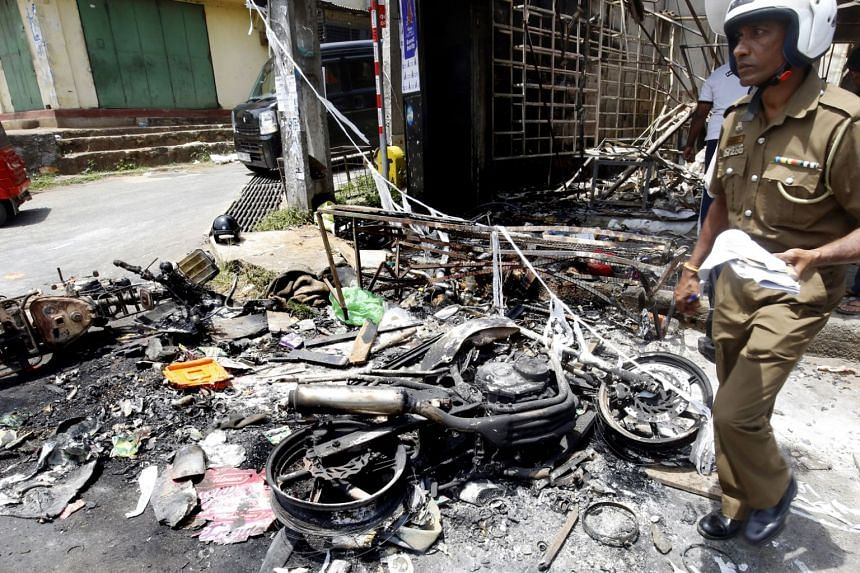 A policeman examines the gutted remains of a business establishment and motorcycles in the riot-torn Digana area in Kandy, Sri Lanka, on March 7, 2018.