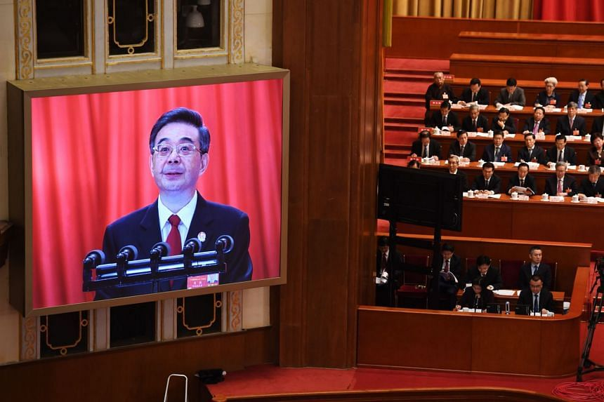 Mr Zhou Qiang, Chief Justice and head of the Supreme People's Court, being shown on screen as he reads the work report during the National People's Congress at the Great Hall of the People in Beijing on March 9, 2018.