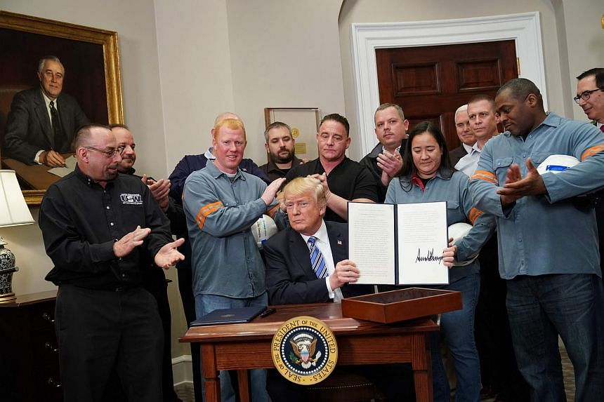 US President Donald Trump holds up Section 232 Proclamations on Steel and Aluminium Imports with his signature, on March 8, 2018.