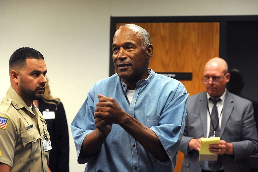 OJ Simpson (centre) reacts after learning he was granted parole during his parole hearing at the Lovelock Correctional Center in Lovelock, Nevada, on July 20, 2017.