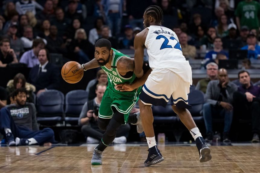 Boston Celtics guard Kyrie Irving dribbles against Minnesota Timberwolves guard Andrew Wiggins in the fourth quarter at Target Center.
