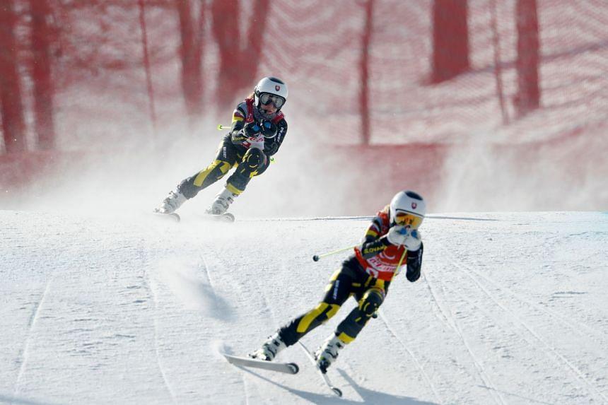 Henrieta Farkasova (rear) competes in the women's Ladies' Downhill Alpine Skiing event, on March 10, 2018.