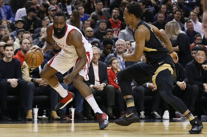 Houston Rockets guard James Harden (left) tries to dribble around Toronto Raptors guard DeMar DeRozan at the Air Canada Centre, on March 9, 2018.