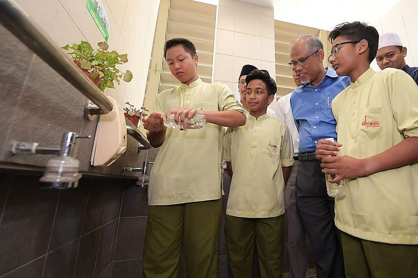 Muhammad Afif Sahernizam, 13, showing Minister for the Environment and Water Resources Masagos Zulkifli how he practises his ablutions in a water-efficient way with a small bottle of water at the Al-Mawaddah Mosque in Sengkang.